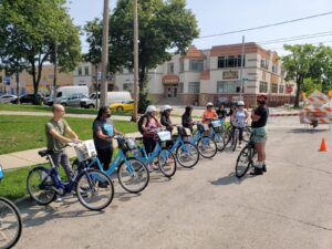 A row of humans and bicycles