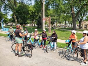 A diverse group of humans standing near bicycles in front of a park